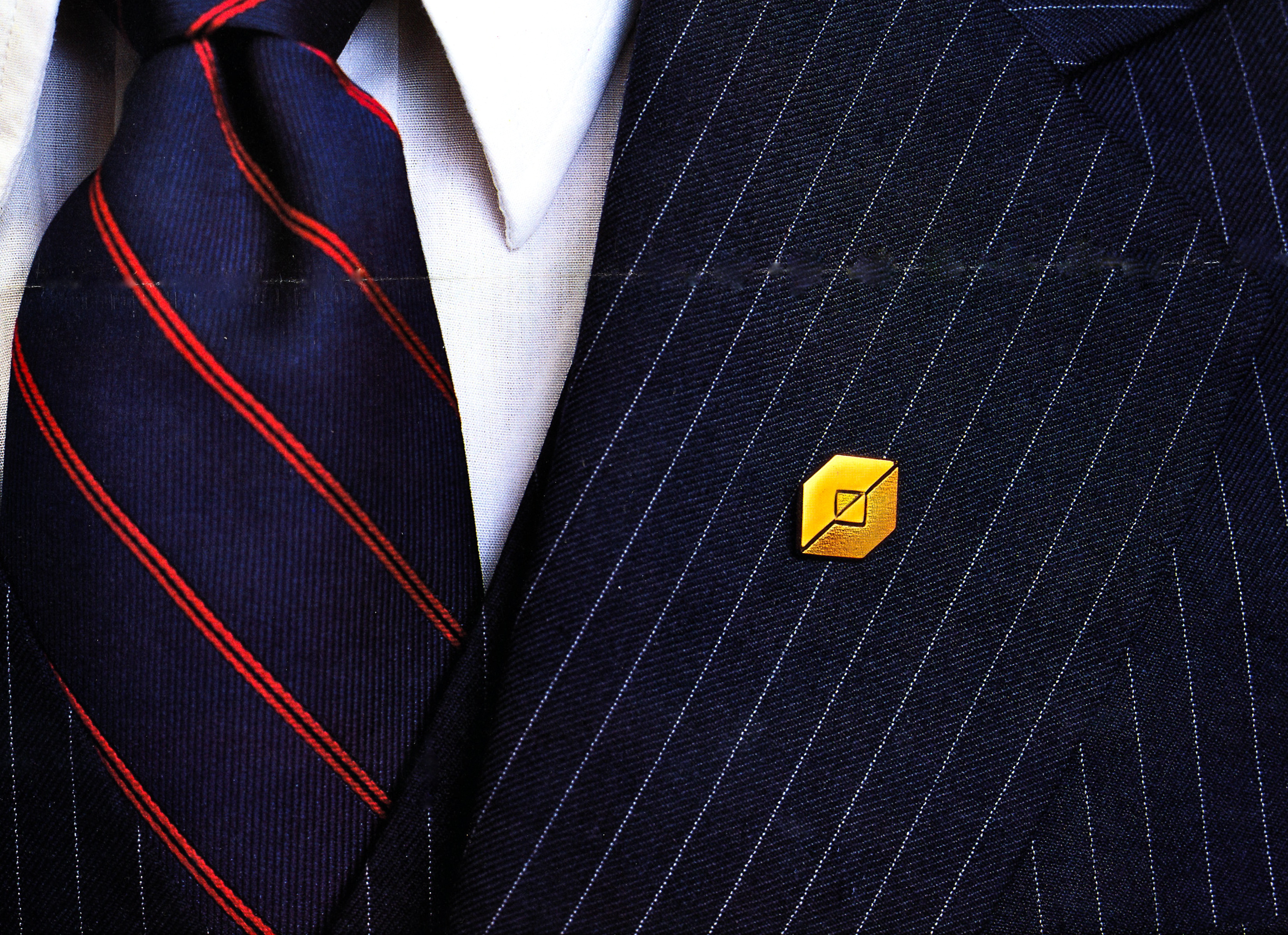 The new Fidelity logo as a gold pot metal lapel pin attached to the lapel of a suit.