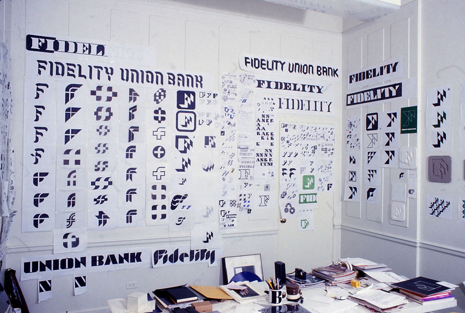 Photo of the office desk of Bill Cannan office desk at 2112 Broadway in New York City surrounded with dozens of hand drawn          design development drawings for the Fidelity logo and typeface illustrating the painstaking process of trial and error          that led to the finished products in the days before computer graphics.