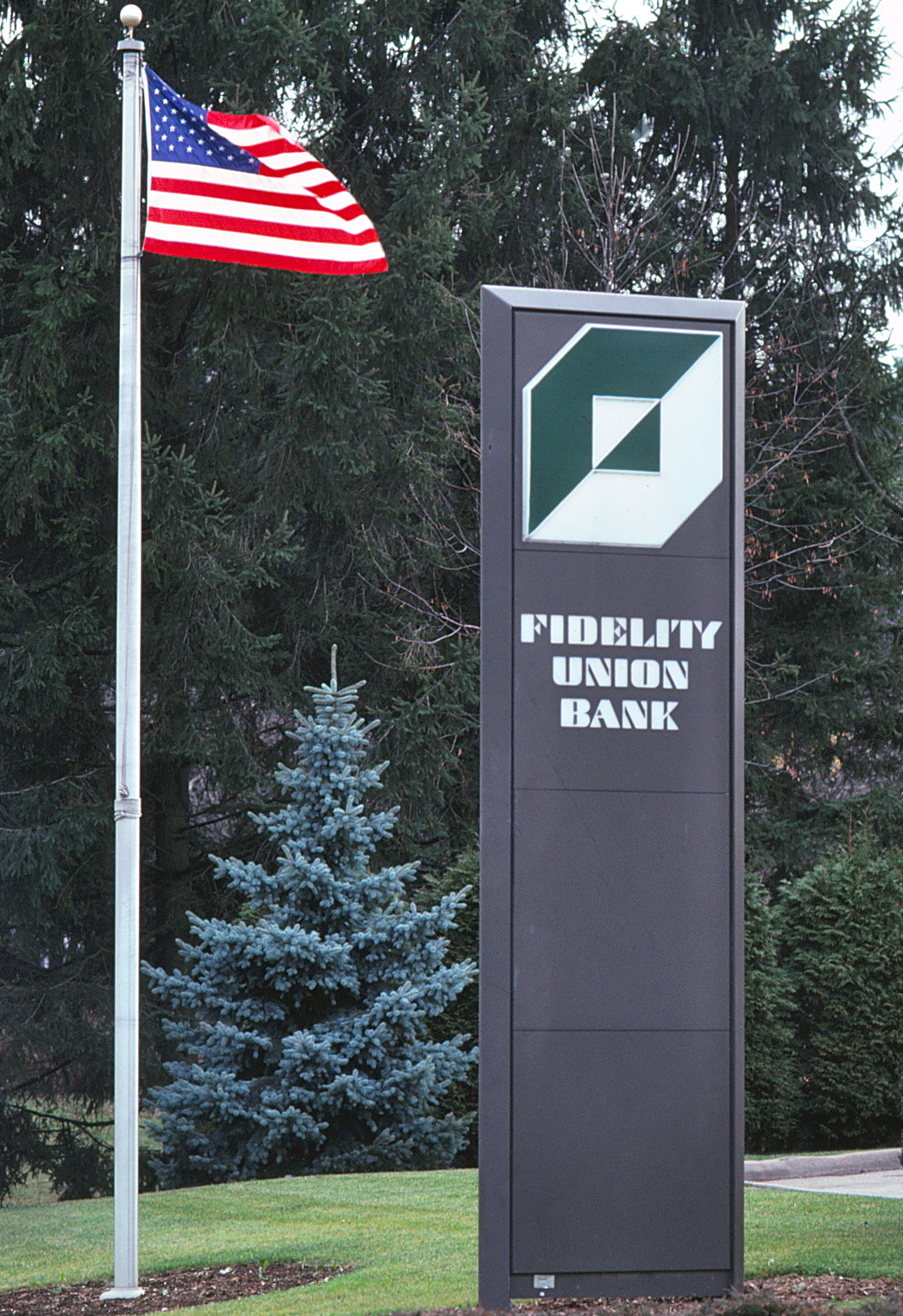 Outdoor photo of a tall pylon with Fidelity logo and typeface next to a fluttering US flag.