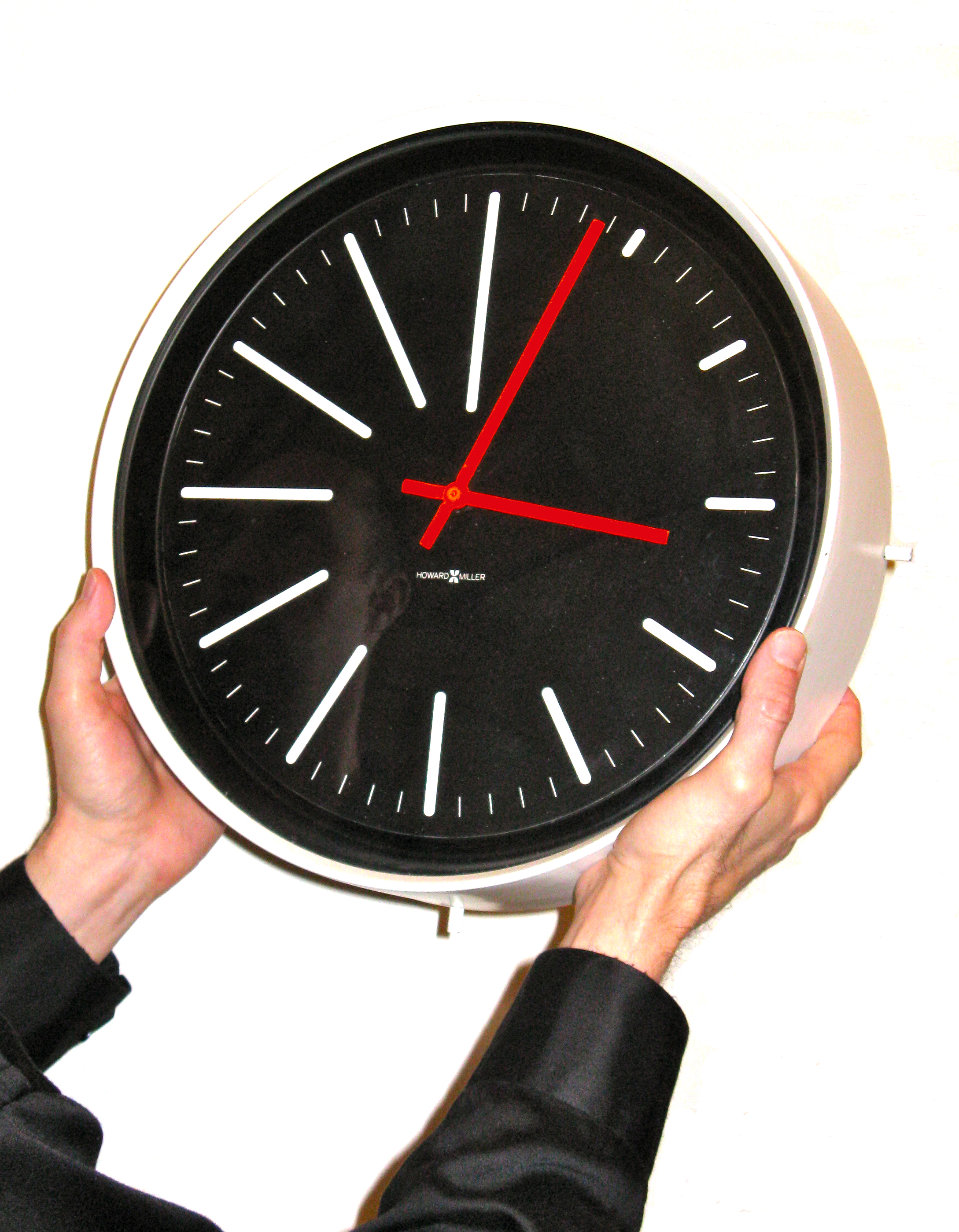 Picture showing a man holding a clock to show scale