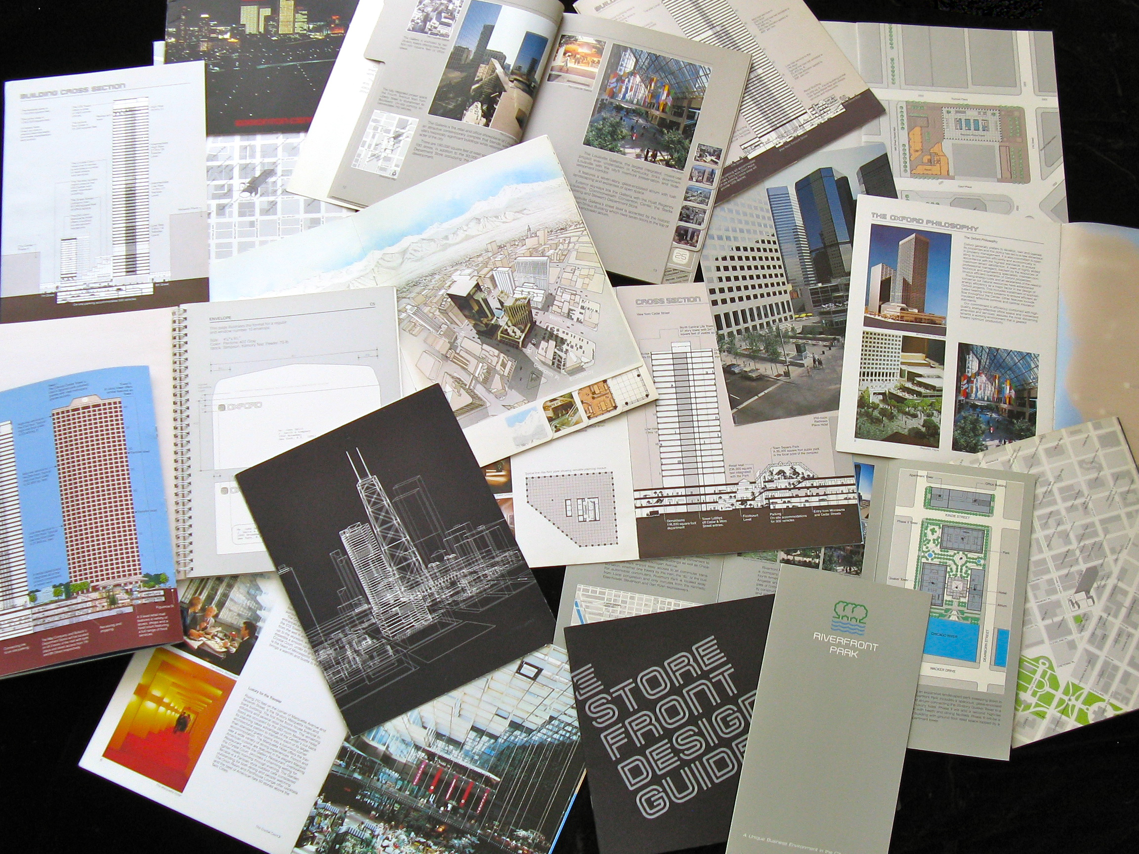 A collection of Oxford Properties brochures spread out on a table.