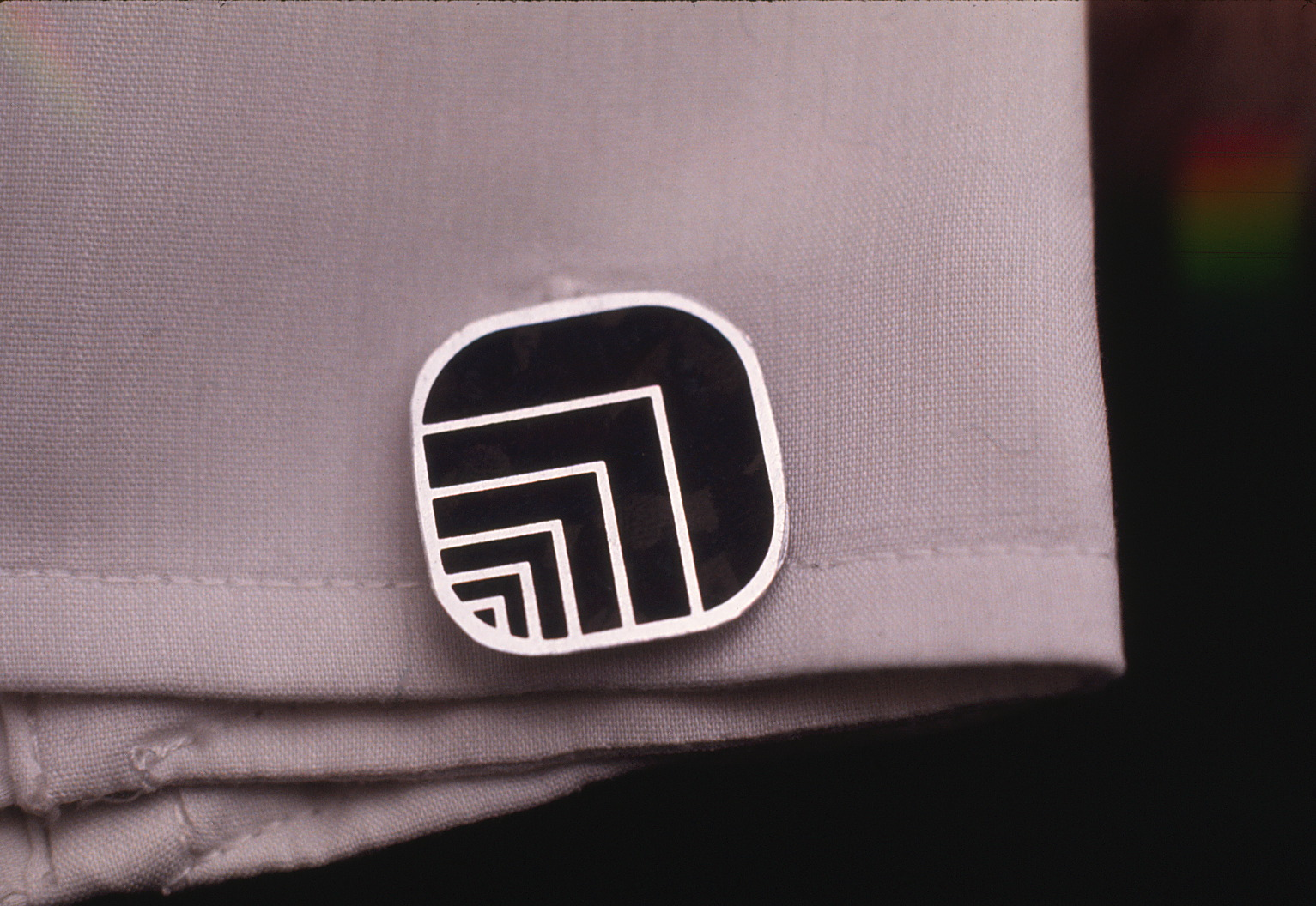 Closeup of cufflink on a sleeve featuring Oxford logo.