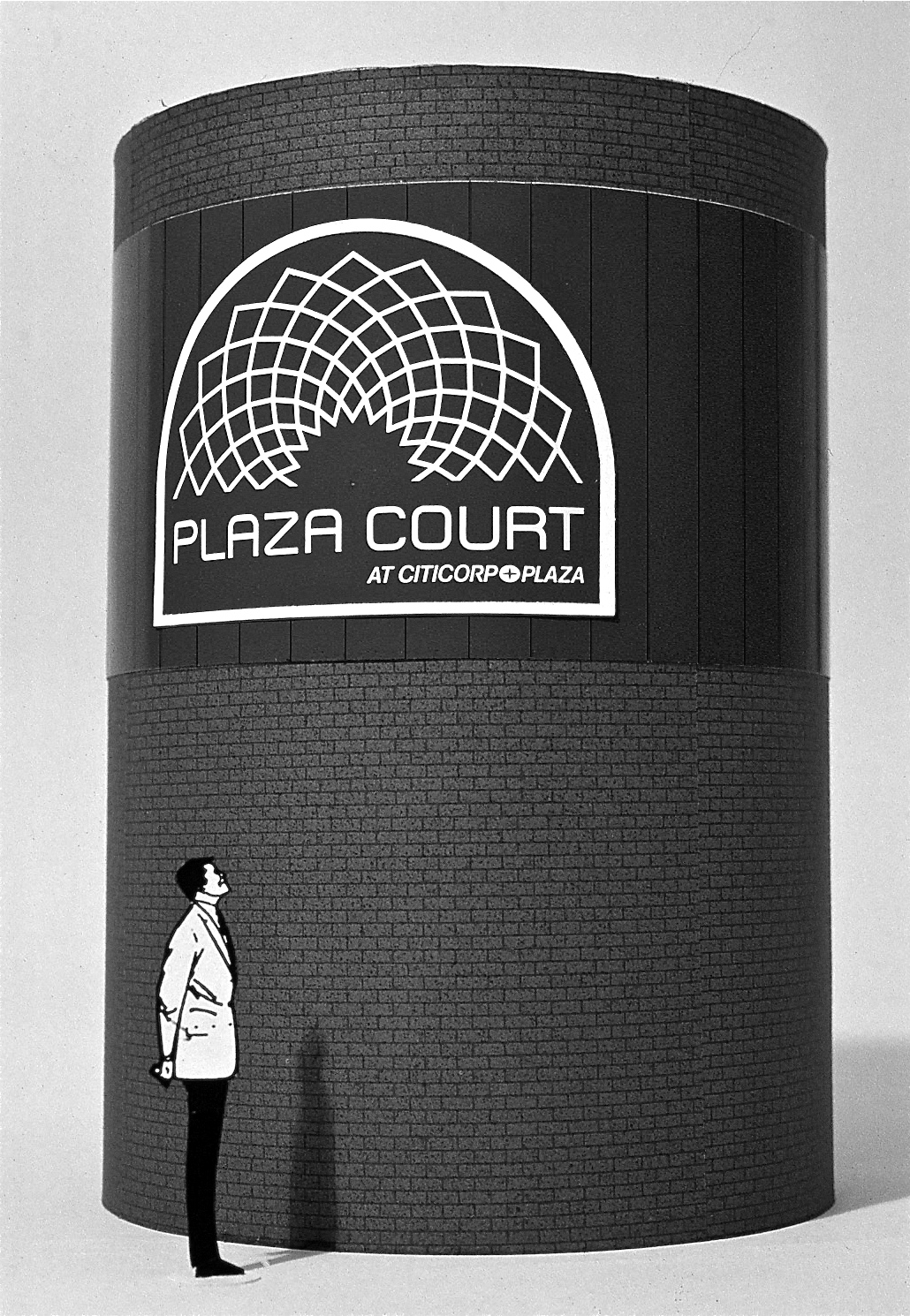 SCale model featuring a man looking up at a large circular brick outdoor ventilation vent with the Plaza Court logo on it.