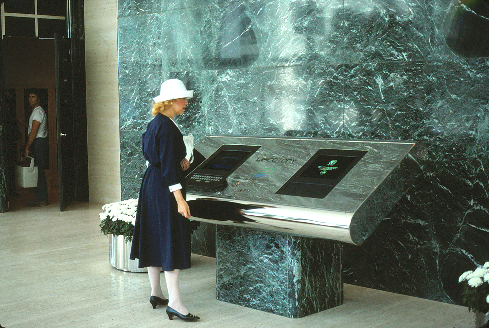 A woman using the interactive directory in the lobby of Quaker Tower.