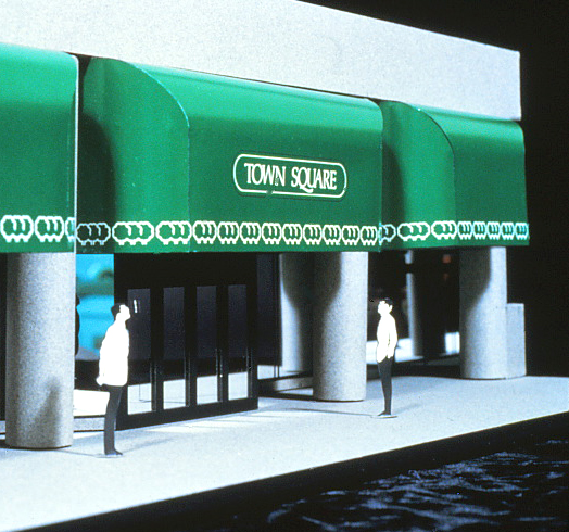 Model of the canopy into the office and retail complex featuring logo and script.