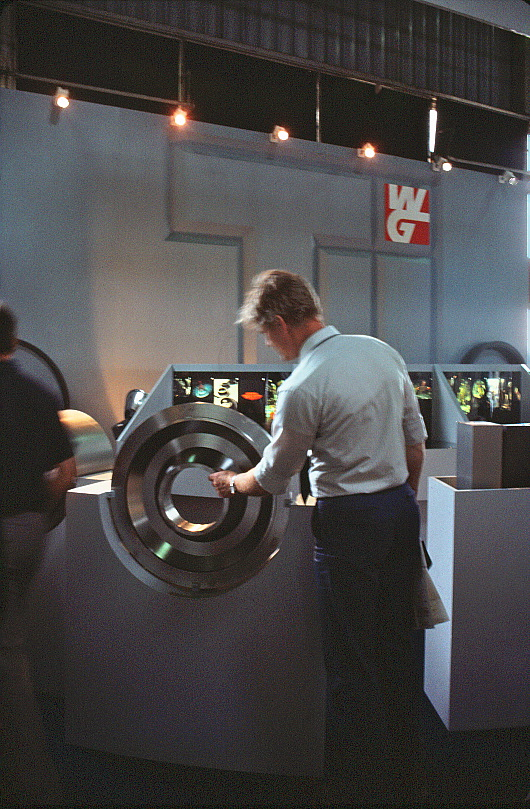 A man inspecting a large, circular metal part.