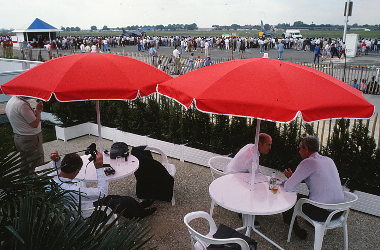 People seated at tables outside near the airstrip beneath large umbrellas.