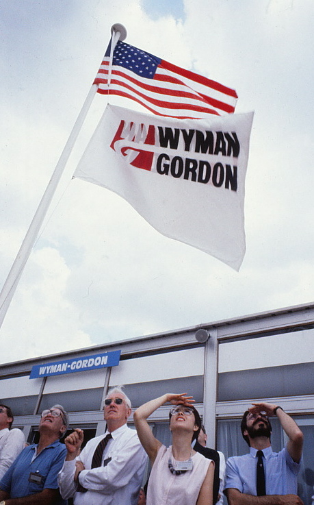 United States and Wyman-Gordon flags on a flagpole outside.