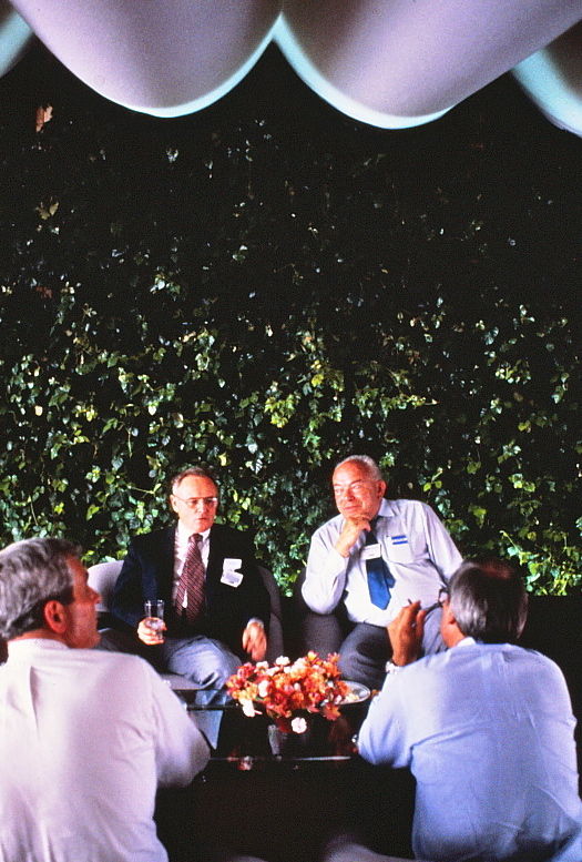 Two men seated and talking in front of the Ivy Wall.