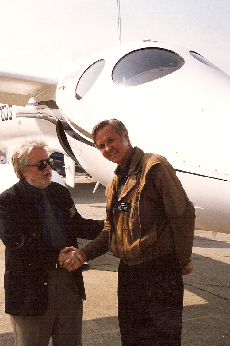 Burt Rutan shaking hands with a journalist.