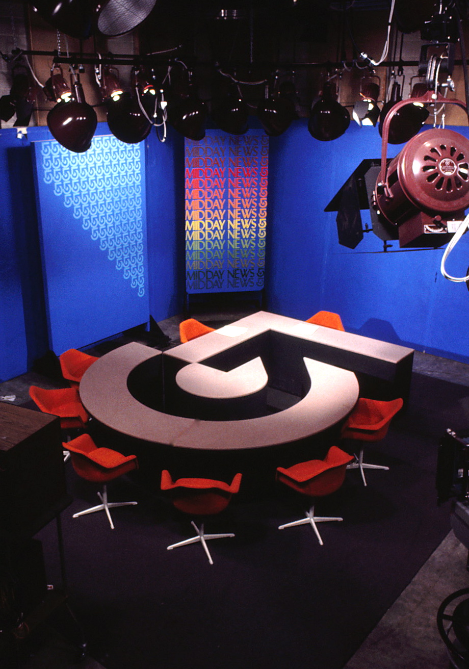 News TV set with table and chairs featuring symbol