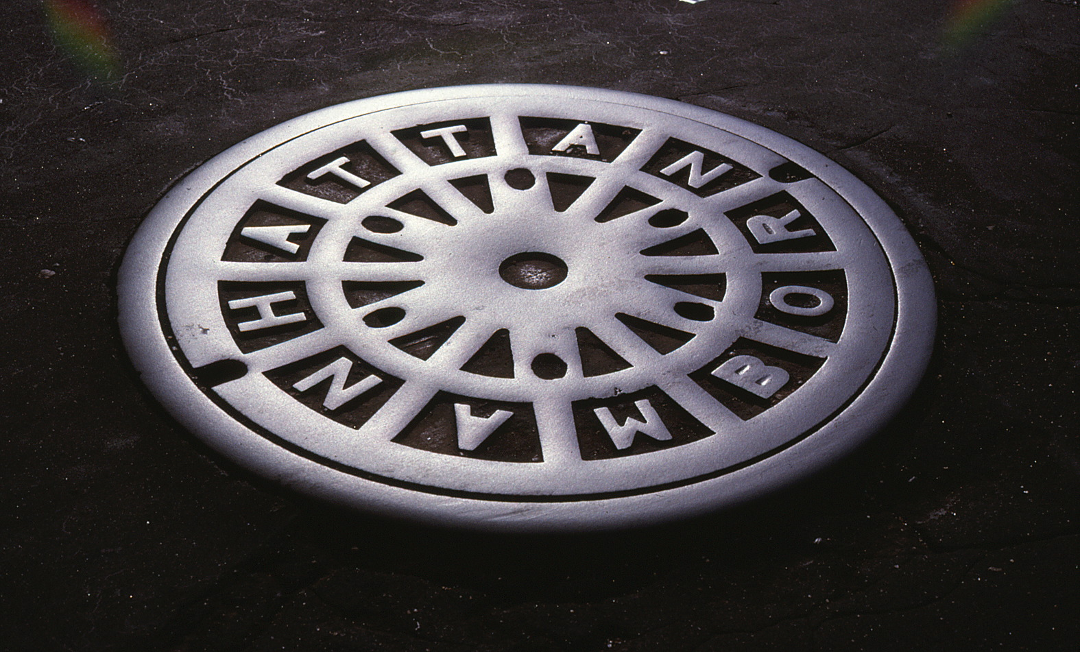 Manhole cover with Manhattan spelled out on it.