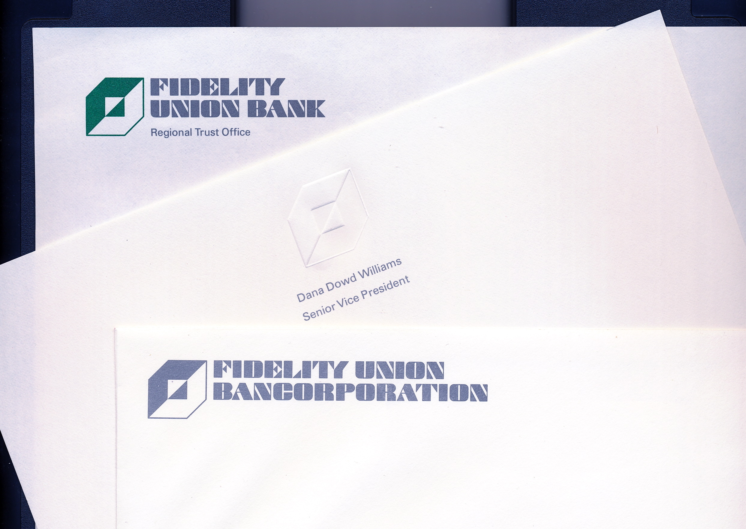 Logo and typface applications atop several pieces of paper.  Three different designs for the new letterhead.