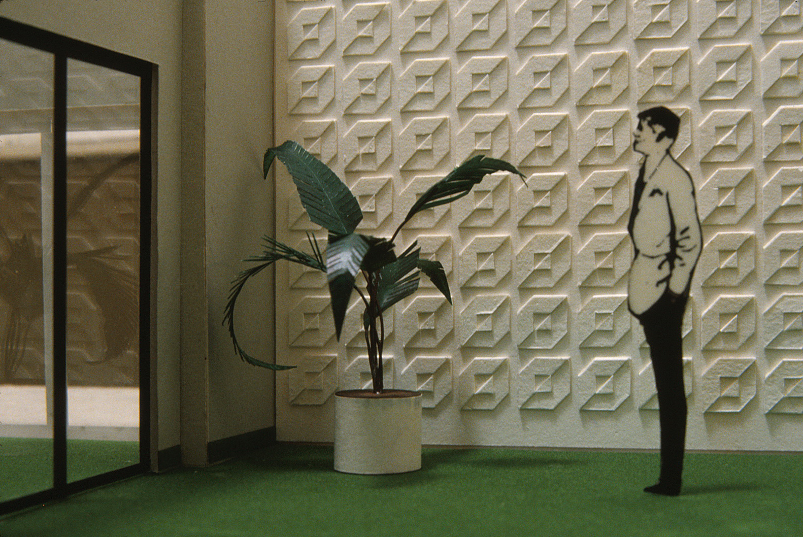 Model of an interior room in corporate headquarters featuring a repeat white on white logo on the wall,          with a plant, a door, and a man standing beside it.