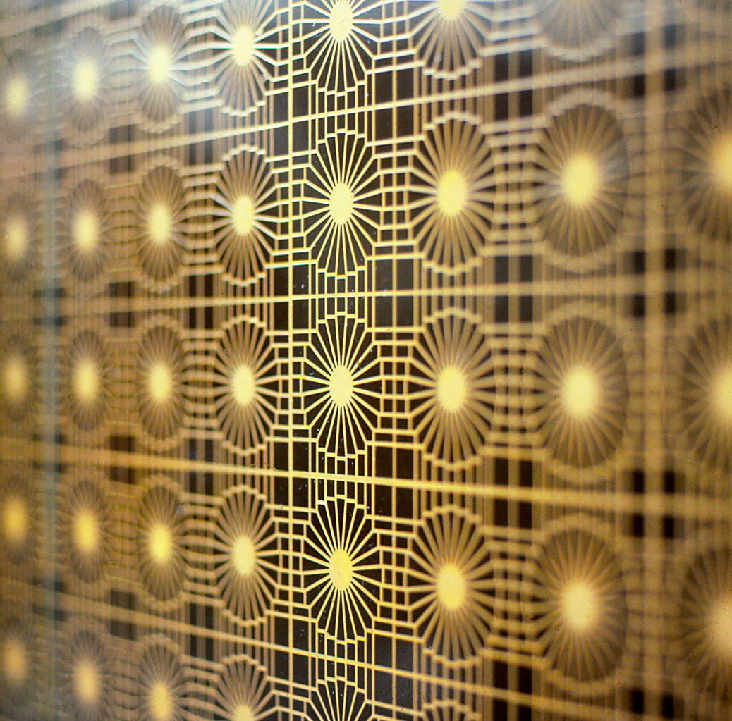 Etched elevator doors featuring repetitive symbols.