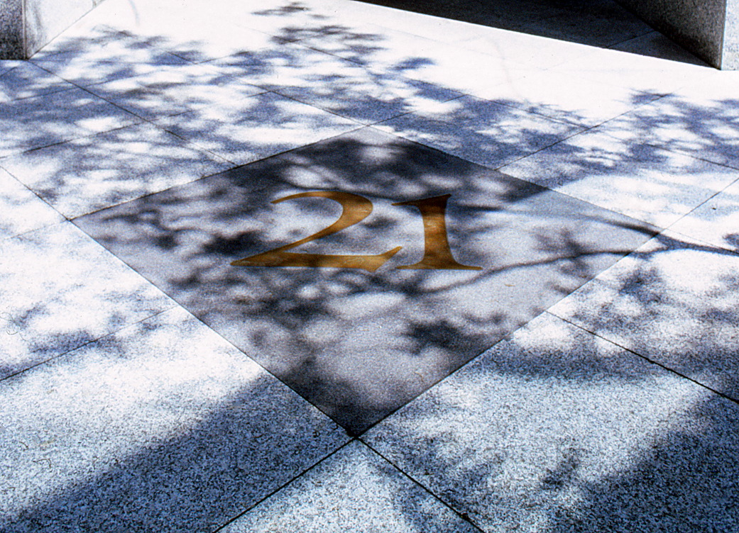 Closeup of the sidewalk featuring the 21 set into it surrounded by a design.