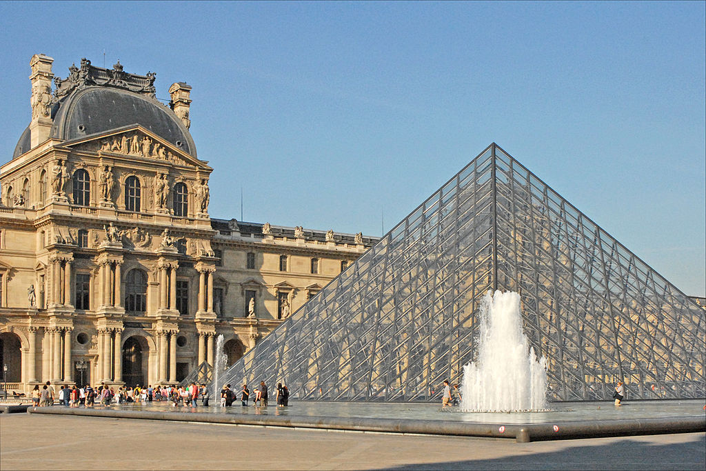 Photograph of the Pavillon Denon in the Louvre Museum plaza, with it's glass pyramid at the center -       	blue sky and white clouds above.
