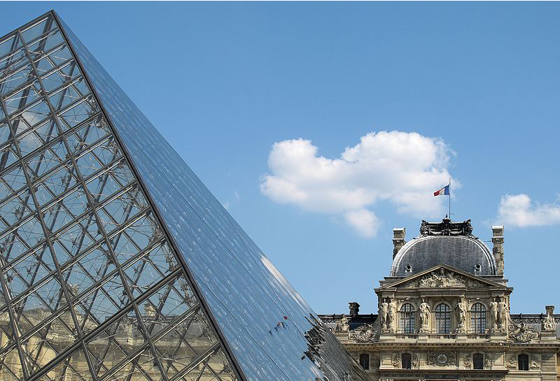 Closeup of the glass pyramid with the Louvre in the background behind it.