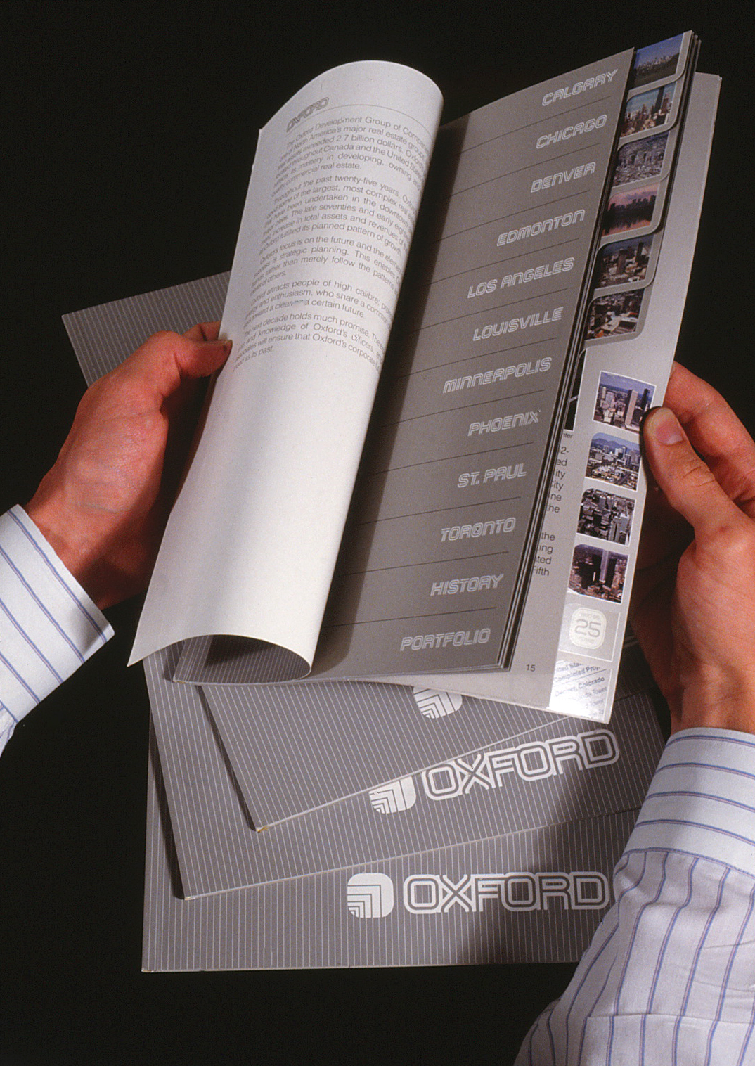 Projects brochure opened by hands and showing the prject names on page three and tabs at right for quick reference to each.