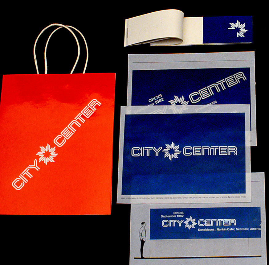 An assortment of folders, booklet and a large bags featuring the City Center logo and signature.