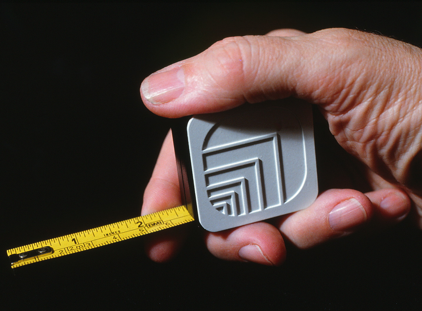Hand holding a tape measure featuring Oxford logo.